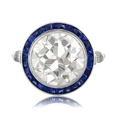 A beautiful Old Mine Diamond with Sapphire Halo Engagement Ring. This engagement ring has a fiery 5.35 carat old mine cut diamond in the center.