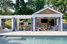 Luxurious pool cabana is partially concealed behind gray grommet curtains framing taupe shiplap walls holding a flat panel television flanked by gold hammered votive holders fixed above a gray wicker sectional placed on a blue striped rug facing a round copper coffee table.