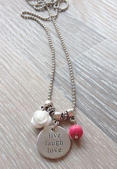 """2mm half lange ball chain met 11mm wit acryl roosje, 8mm roze howliet en een rond metalen plaatje met de tekst """"Live Laugh Love. €6,00"""