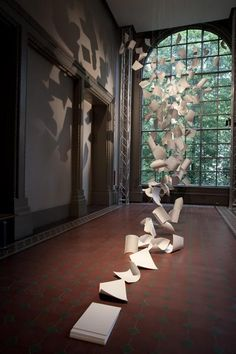 "A Gust of Wind by Pauls Cocksedge is an installation of 300 sheets of corian engraved with the words ""Idea Tray"" and a series number and suspended like sheets of falling paper at the Victoria & Albert Museum for the London Design Festival and given away at the end of the day."