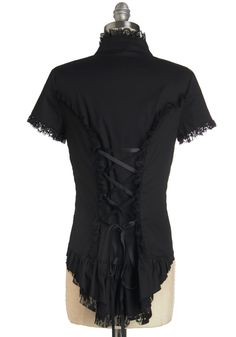 Black poplin top with short set-in sleeves and mandarin collar with black lace edging, center front button loop closure with lace placket, front and rear princess seams with lace accent, rear decorative ribbon lacing, and rear hi-lo hem ruffle with lace edge. 95% cotton/5% spandex, from ModCloth, $44.99