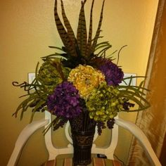 An easy arrangement to make. I made this one for a friend's bathroom. I also have one with reds and golds in my bathrooms. So easy and cheap to make. Hobby Lobby is always putting their flora items 50% off.