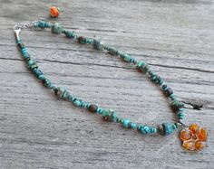 Rehn Designs Beautiful amber flower encased in sterling silver hanging from a strand of turquoise and labradorite with sterling silver lobster clasp and a hand blown glass bead attached to silver chain for adjustable sizing.  19-21 inches long