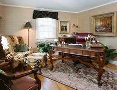 A luxurious office with a large wooden desk, leather chairs, patterned wing chair, regal carpet, dark window treatment, and a wooden sideboard.  Homes designed by Franconia interior designer Randy Trainor. She also serves the New Hampshire Ski Country, Lake Regions and Coast, including Lincoln, North Conway, and Bartlett.