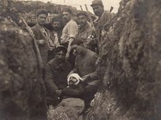 World War I. Wounded French soldier in a trench surrounded by his comrades. Western Front, France, July 1915.