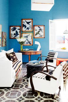 Tour a Pattern-Packed Coastal Bungalow in Morocco // bird artwork, blue walls, geometric tiles, striped throw, eclectic decorating