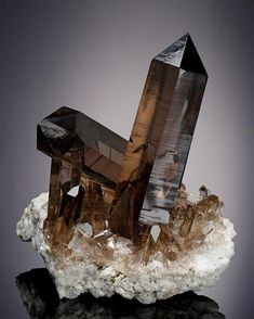 Two excellent crystals of Smoky Quartz display at an angle to each other both very lustrous gemmy with a fine smoky colour measuring to 6cm+. A fine display of Alpine Smoky Quartz, from Switzerland.