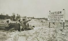 On the Western front of France during World War 1, a car of Ally troops take notice of a multi-lingual sign warning them that the road is monitored by the armies of the Central Powers. ✯