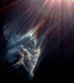 "This image captured by the Hubble Space Telescope shows ""the tendrils of a dark interstellar cloud being destroyed by the passage of one of the brightest stars in the Pleiades star cluster,"" according to the image caption."