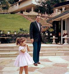 John Wayne with daughter, Aissa, circa 1960, photographed at their ranch-style home in the San Fernando Valley. Pool house is in the foreground with main residence on the hill.