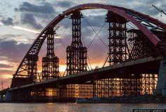 МОСТ С САМЫМ БОЛЬШИМ АРОЧНЫМ ПРОЛЕТОМ(продолжение) Конструкция сооружения Мост относится к типу комбинированных. Конструктивно представляет собой балочную конструкцию, установленную на 30 железобетонных опорах, выполненных на буровых сваях. Длина пролетов — от 40 до 105 метров. Русловые пролётные строения — из металла (неразрезное двухбалочное пролётное строение, с ортотропной плитой), а на подходах к сооружению — железобетонные (сборные балочные).