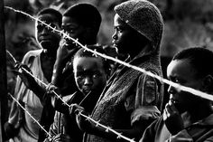 Genocide in Rwanda. Refugees wait behind barbed wire as they watch aid workers unload a new batch of supplies and food, at a refugee camp at the Kigera River border crossing with Rwanda. (Michael S. Williamson/The Washington Post)