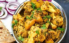 Achaari aloo gobi is an Indian side dish of potato and cauliflower roasted in…