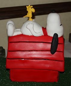 Snoopy sleeping in his dog house on top