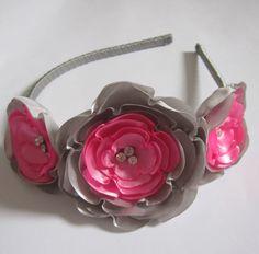 Tiara forrada com fita de cetim, com três flores de cetim cinzas e tons de rosa.