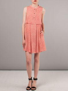 Short, sleeveless nude dress with red and pink floral print, a short mandarin collar with black front buttons to waist, and an overlay panel at seamed waistline. Skirt features front centered box pleat and two hip pleats at front and rear, two side inseam pockets, and a loose fit. 100% Silk. creatures of comfort
