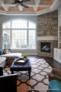 Love the stone fireplace, like the big rug and good paint color (Palladian Blue).