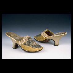 Pair of woman's mules, probably France, 1730-1750. Yellow silk damask embroidered in symmetrical scrolling design using silk knots and satin stitches, as well as silver metallic threads worked in satin stitches over vellum ground to raise it above the surface. Open edge of vamp is bound with gold silk tape and trimmed with ruched pink silk ribbon. The high shaped heel is covered with sueded leather. Leather linings.