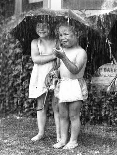 Two young children at Dr. Barnardo's sheltering under an umbrella from a garden shower, 21st June 1934.