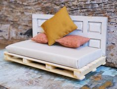Although this is actually a miniature made for a dollhouse, it is a great idea! A day bed made with pallets and an old door.