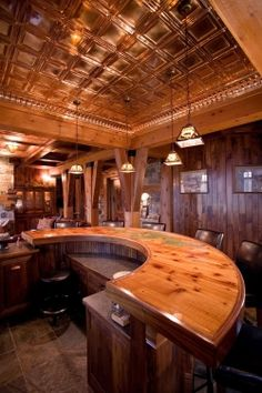 Lodge-style Bar Man Cave, featuring copper ceiling, 180° wrap-around knotty-pine bar, custom cabinetry and slate floors.