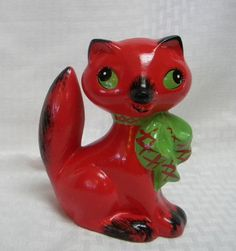 Vintage Pink cat piggy bank ceramic  This pink cat piggy bank is so sweet! She stands about 6 inches tall and is painted a deep hot pink color with green eyes and big green bow around her neck. She is ceramic and still has the made in Japan sticker on bottom