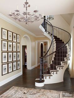 Following the curves of a spiraling staircase, this railing combines plain steel balusters, high-polish wooden handrails, and black iron newel posts. Note how the balusters extend past the steps to fit into brackets, which add jewelrylike sparkle that works with the stair railings to reinforce the staircase's shape.