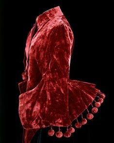 "Red velvet mantle, ca. 1885. Dolmans were cut to lay over the back of the skirt to show off the new bustle fashion of the mid 1880s. This garment was worn by Minnie Fisher (1870-1963), the grandmother of the donor, who was born at the Old Rectory, Bathhampton, Bath. Minnie studied at Gloucester School of Art where she won a ""South Kensington prize"" for still-life painting."