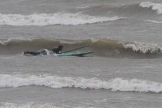 A paddle surfer heads out further on Lake Ontario in Irondquoit until the wave bearing down on him knocks him off his board on Monday, April 23, 2012.    (AP Photo/Democrat and Chronicle, Tina Yee)