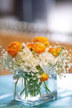 I like the idea with glass and white flowers for a centerpiece. I would have pink instead of orange.