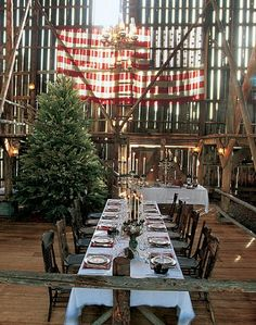 Sun streams in through an American flag to the dining area, which is decorated for a Christmas meal. Sage and willow branches from the ranch grounds adorn the tree. The tablecloth is French lace.
