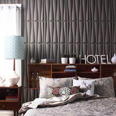 Painel em 3D na cor cinza chumbo complementam o quarto.
