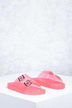 A pair of clear jelly sandals featuring a dual strap design with buckle accents, and a slip-on style. #JellyShoes