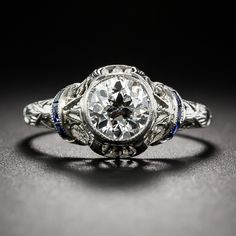 A light, lacy and ultra-lovely early-Art Deco engagement ring, finely hand crafted in platinum - circa 1920s - beams with a bright-white European-cut diamond, weighing 1.02 carats, accompanied by a GIA Diamond Grading Report stating I color - VS1 clarity. The center stone sizzles from within a bezel setting atop a gracefully adorned open work gallery accented with curved bars of royal blue calibre sapphires gracing each shoulder and leading to an artfully engraved upper ring shank. A truly…