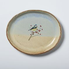 Small handmade oval plate with soft blue and tan glaze and hand drawn blue tit print. Perfect for biscuits or a slice of cake. Measures Length--> 17cm Width--> 13.5cm Height--> 2cm