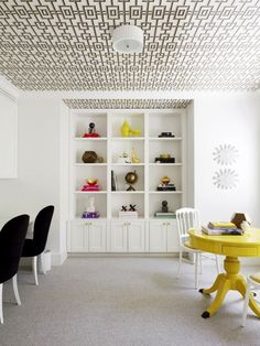 Built-in white bookshelf with wallpapered ceiling and yellow dining table