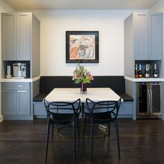 A gray and white breakfast nook gets a punch of color and charm from a custom painting of the homeowners and their sweet dog. The built-in bench is a homey touch; the marble table, hardwood floors and symmetrical arrangement keep the space feeling streamlined and elegant. The space also takes over some of the functions of the counterpart kitchen, featuring an espresso maker, a bar area and a wine refrigerator.