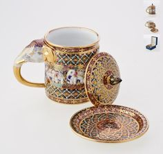 Benjarong elephant mug set - Dork-khem pattern on blue  A Benjarong mug set with elephant bas-relief and handle, complete with lid and saucer. It is made by the technique of craftsmanship originally exclusive for the Thai royal court, with multiple layers of exquisitely hand-painted Thai arts and relief glaze to emphasize its Dork-khem pattern and background against the beautiful 18k gold accent. The elephant bas-relief added another touch of unique Thai culture. Benjarong elephant mug set…