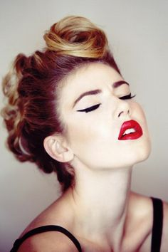 woman with bright red lipstick and bold black eyeliner, closed eyes and face tilted upwards, wearing a black tank top, and retro updo with victory roll