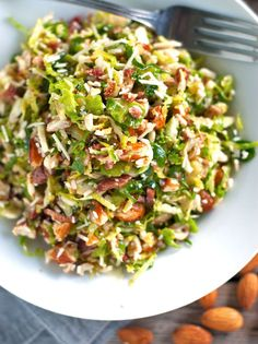 Bacon and Brussel Sprout Salad:1lemon, 1 orange, 1 large shallot, minced, ½ cup olive oil, salt and pepper, 6 slices cooked bacon, crumbled or chopped, 4 dozen brussel sprouts, 1 cup almonds, 1 cup grated Pecorino-Romano cheese