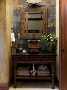 Bold materials and rich colors create a trademark look in this traditional-meets-contemporary bathroom space. The dark wood stain on the classic furniture-style vanity, paired with a copper vessel sink and wall-mount faucet, blends old-world style with modern amenities. Wall treatments and a dramatic ceramic tile backsplash create an undeniable style statement.