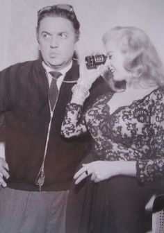 Fellini with Anita Ekberg, looking through photographic viewfinder.