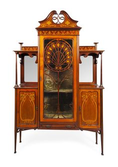 ART NOUVEAU MAHOGANY INLAID DISPLAY CABINET, CIRCA 1910 the pierced surmount above a single glazed door with peacock feather fret decoration enclosing a shelved interior and enclosed by open shelves with mirrored backs and with two cupboard doors below, the whole raised on square tapered legs