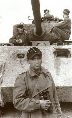"""Der Panzerkommandant eines PzKpfw. V """"Panther"""" der 130.Panzer-Lehr Division plant mit Hilfe einer Umgebungskarte und der Panzerbesatzung das weitere Vorgehen in der Normandie. Im Vordergrund sehen wir mit einem Feldstecher einen weiteren Angehörigen der Panzer-Lehr Division."""