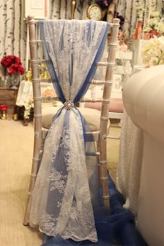 Limewash chiavari chair with blue chiffon and lace wrap with diamante & pearl brooch