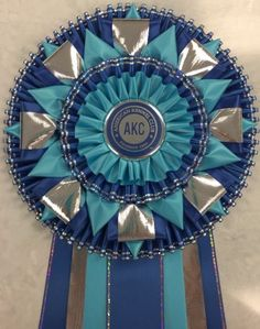 View our collection of ribbons and rosettes available in accents including floral, patterned, glittery golds, silvers and more. Ribbon Rosettes, Ribbons, Centaur, Dog Bows, Diy Candles, Fabric Crafts, Festivals, Homecoming, Photo Galleries