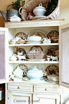 cozy little house Painted cabinet full brown transferware and cow creamers.