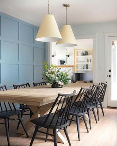 modern farmhouse Dining room with blue paneled walls and long farmhouse rustic dining room table and black windsor chairs with modern pendants in dining room decor, Love the black dining chairs too Dining Room Blue, Black Dining Chairs, Dining Room Walls, Dining Room Lighting, Dining Room Design, Light Wood Dining Table, Colored Dining Chairs, White Chairs, Wood Table