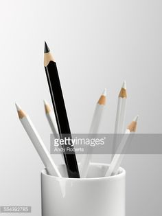 Stock Photo : Tall black pencil in cup with smaller white pencils still life