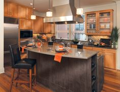 """I know painted white cabinets in kitchens are """"in"""" right now, but we just love the rich warmth of wood. Rift white oak cabinets, glass inserts, accent island=love"""